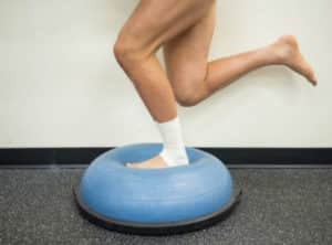 An athlete with a strapped ankle does balance exercises