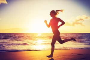 A confident looking woman is running on the Beach with the sun setting over the water