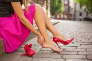 Woman with red high heels sits down and grabs her sore heel.
